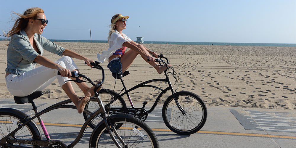 Two women bike down The Strand in Santa Monica, California